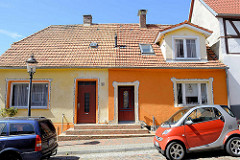 Doppelhaus / Wohnhaus in der Mühlenstraße von Ribnitz-Damgarten; farblich mittig geteilt, gelb + orange - Mosaik Verzierung um Türen und Fenster