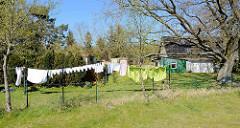Wohnhaus mit einzelnd stehenden Einraum-Ferienhäusern - Wäsche hängt zum Trocknen auf der Leine; Ostseebad Zingst, Mecklenburg-Vorpommern.