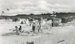 Historische Aufnahme vom Badeort, Ostseebad Zingst - Sandburgen mit Strandkörben, Kinder spielen in Kleidung, Matrosenanzug im Sand; Flaggen Deutsches Reich und Flagge Deutsche Kaiserliche Marine wehen am Strand.