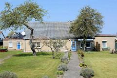Wohnhaus mit Vorgarten / Rasen im Ostseebad Zingst, Mecklenburg-Vorpommern; Spitzdach / Satteldach - graue Putzfassade; lks. und re. Anbauten für Ferienunterkünfte.