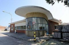 Pförtnerhaus, Einfahrt eines Gewerbegeländes / Industriegebiets in Hamburg Harburg - Architektur der 1960er Jahre; runde gekachelte gelbe verglaste Fassade - überstehendes Flachdach.