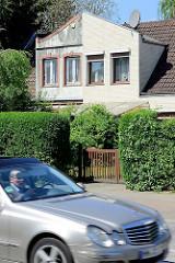 Neu + Alt; Doppelhaus Alter Zollweg in Hamburg Rahlstedt - unterschiedliche Fassadengestaltung, fahrender silberner Mercedes.