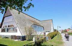 Wohnhaus am Süderende - bis zum Boden reichendes Reetdach - Fahrradfahrer; Bilder der Ostseeinsel Hiddensee, Mecklenburg-Vorpommern.