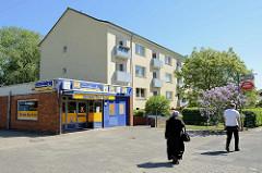 Wohngebäude der 1960er Jahre mit vorliegendem Flachbau für Einzelhandel - Bei der Windmühle in Hamburg Wilhelmsburg.