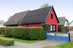 Ferienhaus mit roter Hausfassade, Satteldach mit Wellblech - daneben Ziegeldach und im Hintergrund Reetdach - Ostseebad Zingst, Mecklenburg-Vorpommern.