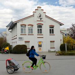 Seestraße / Klosterstrasse - Gebäude mit Stufengiebel, Ostseebad Zingst - Mecklenburg Vorpommern, Radfahrerin mit Kinderanhänger.