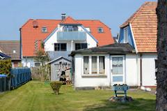 Wohnhäuser im Ostseebad Zingst, Mecklenburg-Vorpommern; Hausanbau mit einem Raum, Gardinen vor Fenster und Tür; ehem. Ferienzimmer.