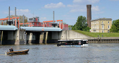 Hamburger HafenCity RiverBus auf seiner Sightseeing-Tour in der Billwerder Bucht am Sperrwerk von Hamburg Rothenburgsort. Rechts der historische Wasserturm - 1848 errichtet.