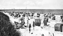 Historisches Bild aus dem Ostseebad Prerow - Familien sitzen im Sand am Strand der Ostsee, Badekleidung ist zum Trocknen auf Stöcken aufgehängt - Strandkörbe stehen in Sandburgen.