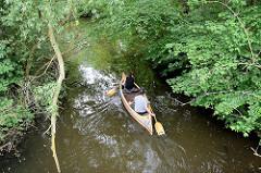 Wasserlauf Rathauswettern zwischen Erlen - Wasserweg in Hamburg Wilhelmsburg / Inselpark; ein Kanu fährt auf dem Kanal.