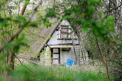 Leerstehendes Wochenendhaus / Ferienhaus mit tief herunter gezogenem Reedach im verwildertem Garten - Ferienhäuser im Ostseebad Zingst, Mecklenburg-Vorpommern.