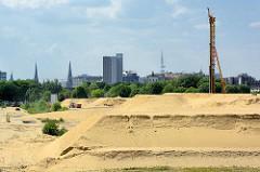 Ehem. Huckepackbahnhof in Hamburg Rothenburgsort - Bauvorbereitung, Aufschüttung des Areals mit Sand. Das 11 Hektar große Gelände ist Teil vom Stadtentwicklungskonzept Stromaufwärts an Elbe und Bille. Im Hintergrund Türme der Hansestadt Hamburg.