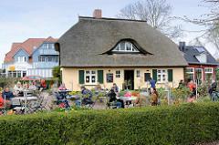 Gartenlokal, Gäste sitzen im Blumengarten an Tischen in der Sonne - Reetdachhaus mit Dachfenster