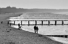 Strandszene in Schwarz-Weiß, Spaziergänger am Strand vom Ostseebad Zingst - Holzbuhnen ragen ins Wasser.