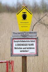 Hinweisschild an den Sundischen Wiesen - Nationalpark Vorpommersche Boddenlandschaft, Kernzone. Weg betreten und befahren verboten; Kampfmittelbelastetes Gebiet Lebensgefahr. Die Sundischen Wiesen  bilden den östlichen Teil der Halbinsel Zingst.