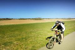 Fahrradfahrer auf dem Deich bei den Sundischen Wiesen auf der Halbinsel Zingst. Die Sundischen Wiesen oder auch die Sundische Wiese bilden zusammen mit dem Pramort den östlichen Teil der Halbinsel Zingst im Landkreis Vorpommern-Rügen.
