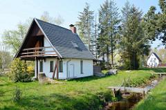 Einzelhaus / Wochenendhaus mit hohem Dachausbau und Balkon - Graben mit Holzsteg; Ferienhäuser in im Ostseebad Zingst, Mecklenburg-Vorpommern.