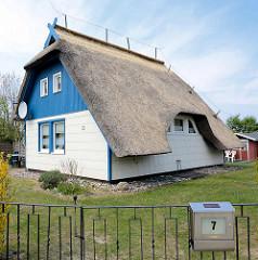 Ferienhaus mit Reetdach - ausgespart am Seitenfenster, im Dachgeschoss blaue Holzfassade / Ostseebad Ahrenshoop.