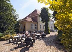 Das Museum Elbinsel Hamburg-Wilhelmsburg hat seinen Sitz im alten Hannoversche Amtshaus. In seinen Räumen zeigt das Regional-Museum die Geschichte und bäuerliche Kultur Wilhelmsburgs. In dem Museumscafè sitzen Gäste auf dem Kopfsteinpflaster.