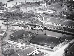 Historische Luftaufnahme vom Marktkanal in Hamburg Veddel. Frachtschiffe liegen am Kanalufer, Lagerhäuser mit Krananlage - im Hintergrund die Norderelbe.