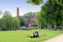 Wiese / Liegewiese am Ende vom Veringkanal in Hamburg Wilhelmsburg - im Hintergrund die Honigfabrik; 1906 als Magarinefabrik erbaut - jetzt Kulturzentrum.