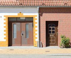 Hauseingänge unterschiedlich gestaltete Fassaden, Nördlicher Rosengarte / Ribnitz-Damgarten; weisse Hausfassade mit gelb abgesetztem Eingang / Ausfahrt - Ziegelfassade.