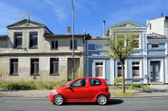 Architektur in Ribnitz-Damgarten, Bahnhofsstraße - restauriertes Wohnhaus mit blauer Fassade, weiss abgesetzten Fensterlaibung -  verlassenes Wohnhaus, gleiche Bauform wie das Nebengebäude, verfallene Hausfassade - alt + neu.