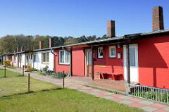 Schlichtwohnungen, Reihenhäuser mit Flachdach und hohem Schornstein - teilweise rote Hausfassaden, beim Kiefernweg in Barth.