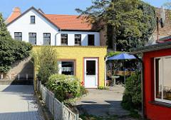 Kleine Ferienwohnung im Hinterhofschuppen mit gelber Fassade und Wellblechdach - Architektur in Barth / Mecklenburg Vorpommern.