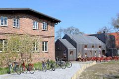 Historische und moderne Architektur - Ziegelgebäude und Holzfassade; Humunkulus Figurensammlung auf der Ostseeinsel Hiddensee / Vite.