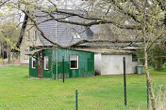 Wohnhaus mit einzelnd stehenden Einraum-Ferienhäusern / Schuppen mit Wellblech eingedeckt.