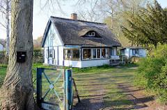 Mit Reet gedecktes Ferienhaus / Wochenendhaus mit ausgebautem Dach, Dachfenster / Ochsenauge; mit Blau abgesetzte weiße Fassade; Ostseebad Prerow.