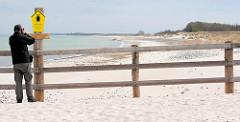 Holzzaun, Abgrenzung am Strand auf der Halbinsel Zingst - Hinweisschild Nationalpark Vorpommersche Boddenlandschaft, Kernzone - Brut-, Rast- und Überwinterungsgebiet - Betreten verboten. Ein Fotograf fotografiert das Schild.