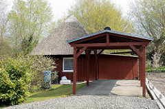 Kleines reetgedecktes Holzhaus, Ferienhaus mit großem Carport, dahinter Einfahrt zur Garage.