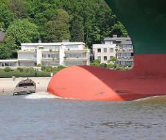 Wulstbug vom Containerfrachter Thalassa Axia auf der Elbe vor Hamburg Blankenese; am Strand ein altes Schiffswrack. Der Containerfrachter wurde 2014 gebaut und kann 13 808 TEU Standardcontainer transportieren.