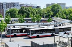 Blick auf den Busbahnhof Hamburg Wilhelmsburg - ein Gelenkbus steht an der Haltestelle, ein weiterer Bus fährt ab.