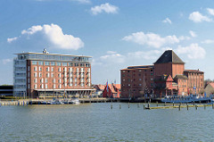 Re. das denkmalgeschützte Speichergebäude mit Bandbrücke am Hafen / Osthafen von Barth; Industriedenkmal, das zum Apartmenthaus umgebaut werden soll. Lks. das zu einem  Hotel umgebauter Speicher.