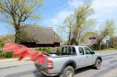 Reetdachhäuser an der Dorfstraße von Ahrenshoop - Pickup in Fahrt mit flatternden roten Fischereiflaggen.