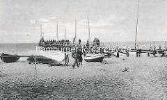 Historisches Bild vom  Ostseebad Zingst - eine Holzbrücke, Seebrücke führt ins Wasser - Menschen stehen auf dem Steg; am Strand liegen Ruderboote, Fischerboote.