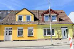 Restaurierte Wohnhäuser mit ausgebautem Dach - Doppeldachfenster und unterschiedlich gelb gestrichene Hausfassade; Bahnhofstraße in Ribnitz Damgarten.