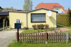 Einraum / Einzimmer Ferienhaus mit großem Fenster / Satellitenschüssel an der Hauswand in Zingst, Mecklenburg-Vorpommern.