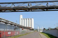 Industriestrasse im Gewerbegebiet / Hafengebiet von Hamburg Harburg - Rohrleitungen überqueren die Straße, hohes weisses Silo.