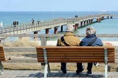Seebrücke im Ostseebad Prerow - ein Paar sitzt auf einer Holzbank und blickt auf die Ostsee.