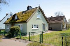Wohnhaus mit bemoostem Reetdach - dahinter schmaler Schlichtbau als Ferienwohnung genutzt; Ostseebad Zingst, Mecklenburg-Vorpommern.