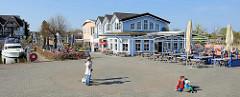 Hafen von Zingst am Barther Bodden in Mecklenburg Vorpommern - Hafenpromenade mit Restaurants, Aussengastronomie.