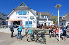 Hafenpromenade von Vite auf Hiddensee, Mecklenburg Vorpommern. Fischhalle / Fischimbiss - Restaurant mit Tischen in der Sonne.