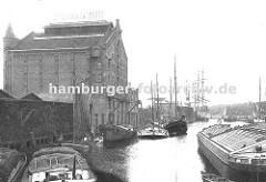 Fabrikationsanlage und Lagergebäude der 1896 gegründeten Leinöl und Firniswerke HOBUM ( Harburger Oelwerke Brinkman & Mergell) am Harburger Ziegelwiesenkanal; Binnenschiffe und Frachter am Kai.