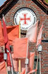 Ziegelgebäude, Emblem DIE SEENOTRETTER - rote Signalflaggen der Fischerei wehen im Wind; Hafen von Vite - Hiddensee, Mecklenburg Vorpommern.