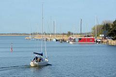 Ein Segelboot fährt unter Motor in den Zingster Hafen ein - im Hintergrund liegt ein modernes Hausboot am Ufer.