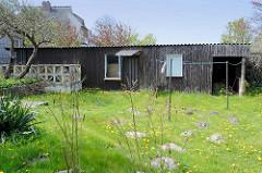 Altes Holzgebäude mit Wellblech als Dach - Terrasse mit Betonwand und diagonalen / dreieckigen farbigen Glassteinen - ehem. Ferienhaus im Ostseebad Ahrenshoop.
